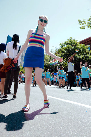Girl wearing rainbow clothes and Pride Slides outside at pride parade