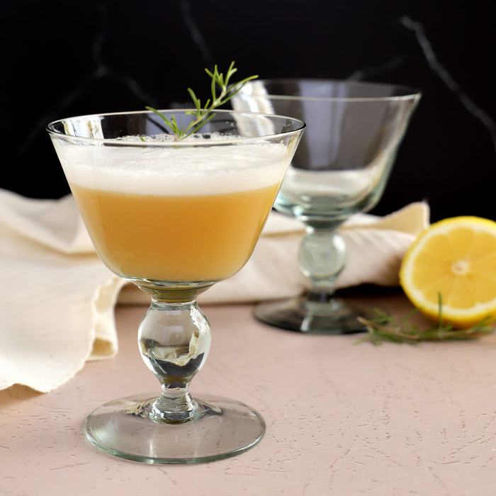 Whiskey sour cocktail recipe with egg white, in recycled glass coupe glasses