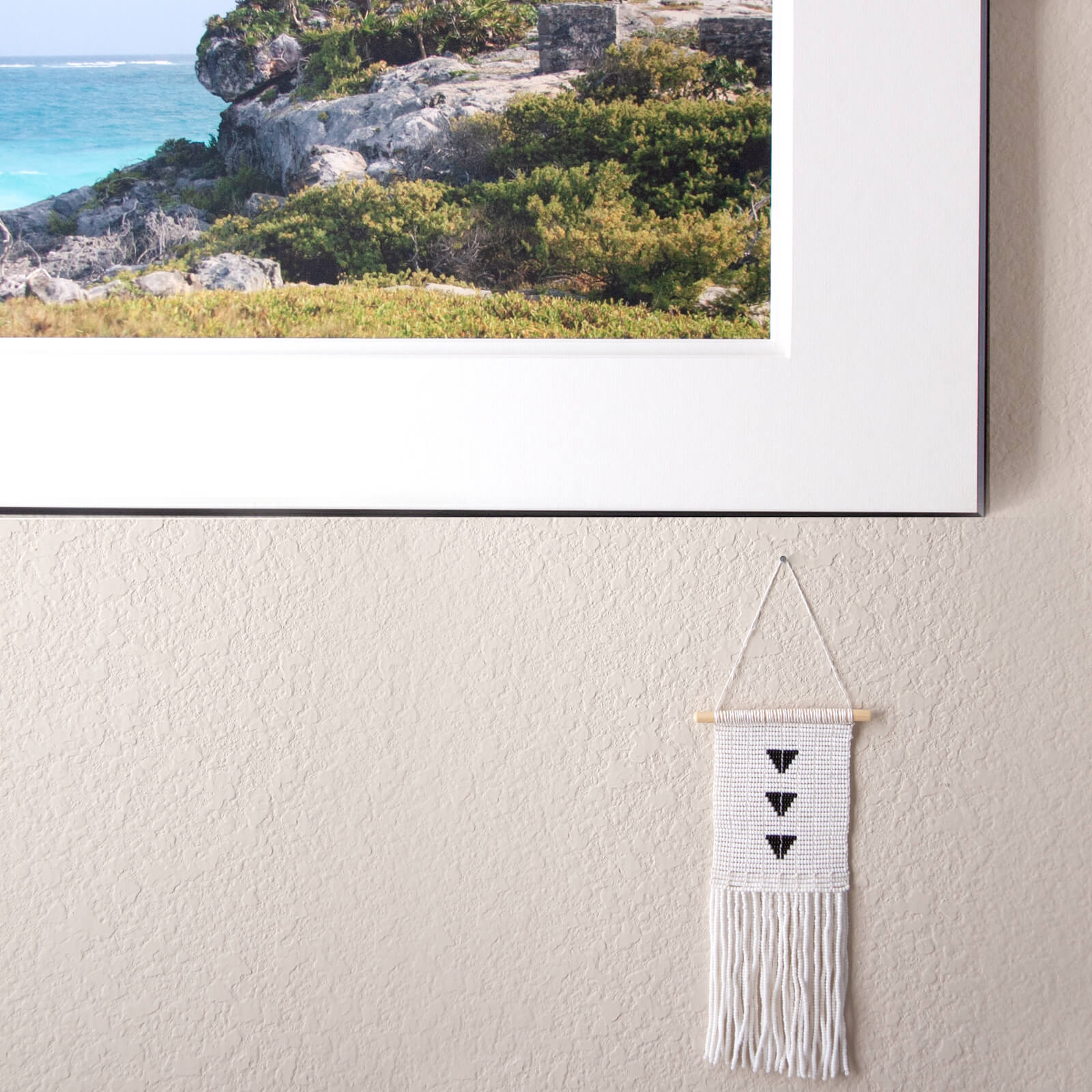 Little white wall hanging with tiny black triangles made of beads