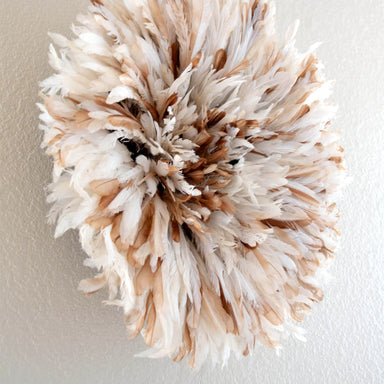 Small White and Tan speckled Authentic African juju hat hanging on the wall