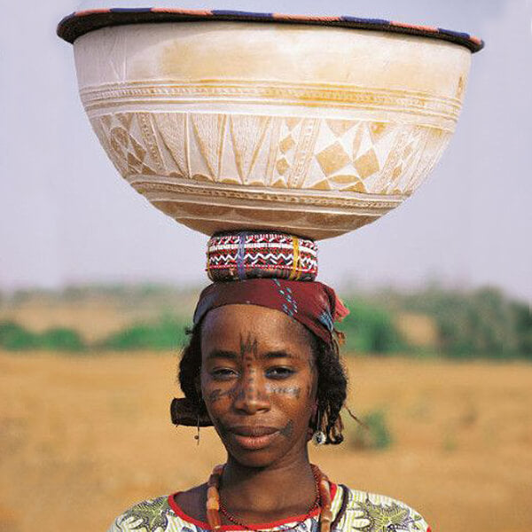 Woman balancing an Authentic African Fulani calabash bowl with white painted pattern details on her head