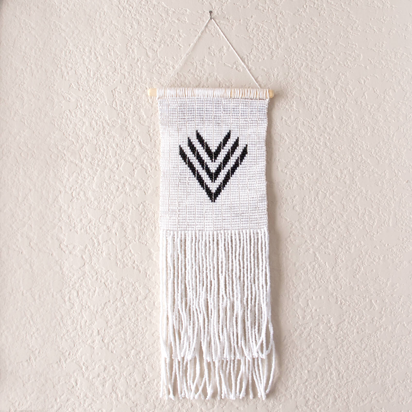 Black and white beaded wall hanging made by Tanzanian Maasai artisans  with three v shapes