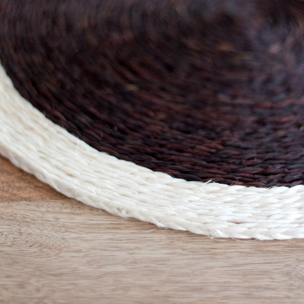 Detail shot of the edge of a hand woven circle placemat in chocolate brown and cream trim