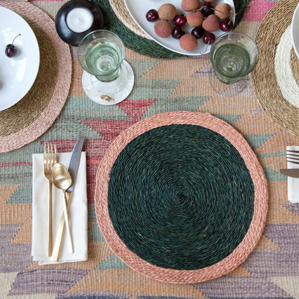 Styled shot of a hand woven circle placemat in olive green with blush pink trim on a dining room table