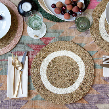 Styled shot of a hand woven circle placemat in natural tan with white circles inside on a dining room table