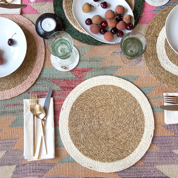 Gone Rural Swaziland hand woven circle placemat in natural tan with white trim styled in a dining room