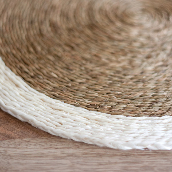 Detail shot of the edge of a Gone Rural Swaziland hand woven circle placemat in natural tan with cream trim