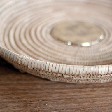 Side view of a Touareg medallion basket made of palm leaf and silver with etched details