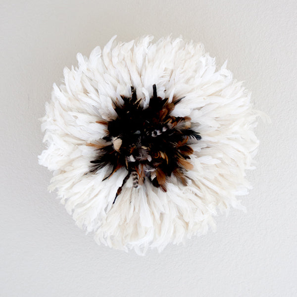 small white authentic African juju hat with a cluster of dark feathers in the center