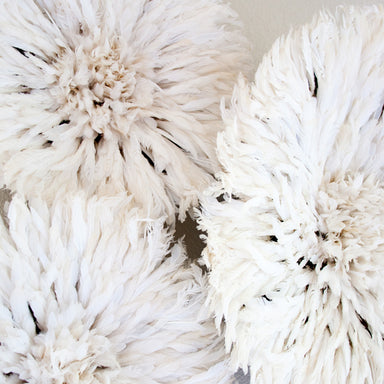 close up of three white African feather wall hangings