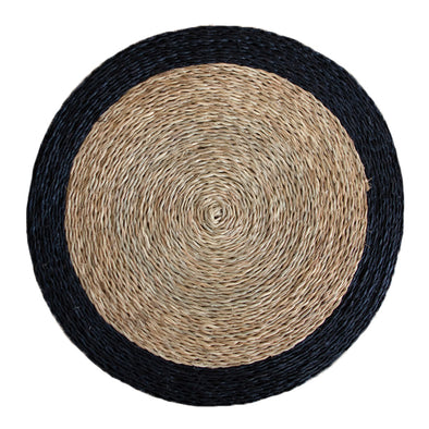 Hand woven circle placemat in natural tan with black trim