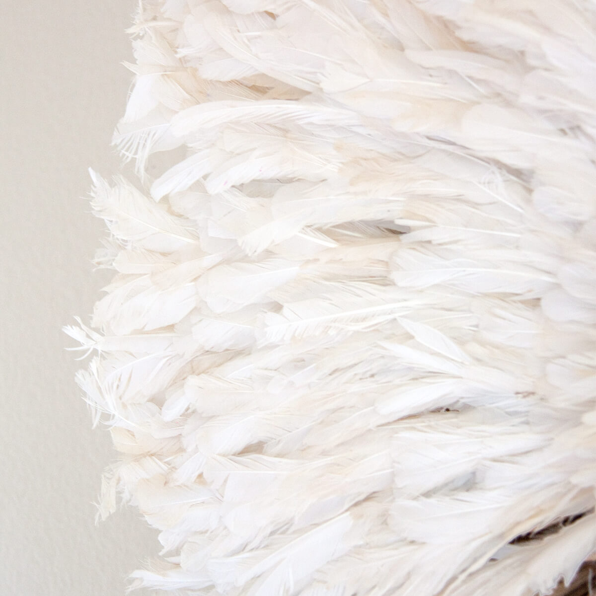 Detail of the feathers on the edges of an Authentic African Juju hat in creamy white natural feathers