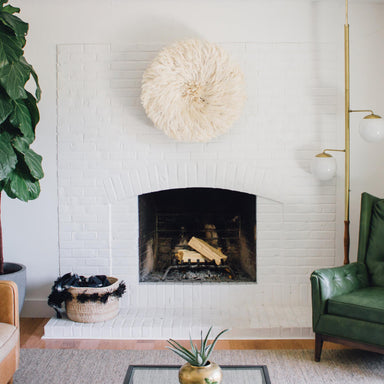 Modern hearth with a white juju hat hanging over the fireplace