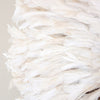 Close up view of the side of an authentic African juju hat in a warm, creamy white color