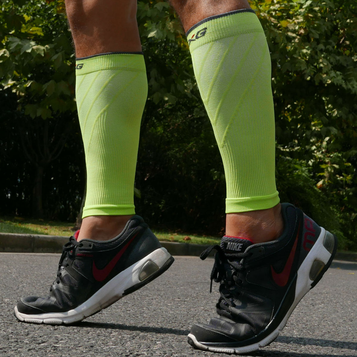 6aa6e540a ... Male runner wearing TXG calf compression sleeves in yellow ...
