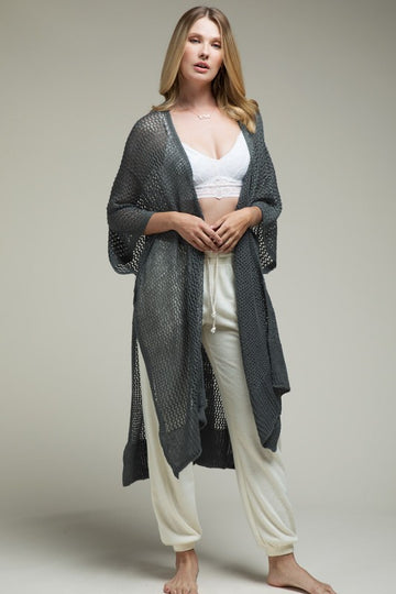 Wrap yourself in style! This light open knit Ruana wrap has cool caftan sleeves and side slits. Pairs perfectly with a tee and jeans or wear it for a cozy vibe with your loungewear. Acrylic. Model is approx 5'9
