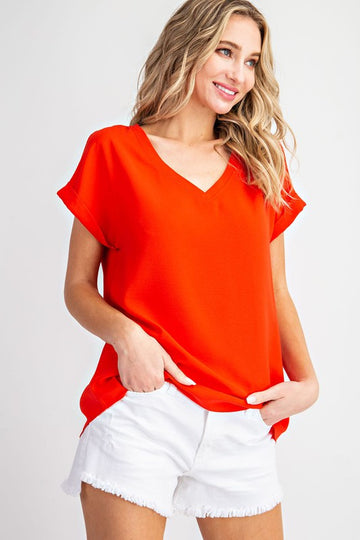 This easy fitting top has an everyday wearable look. Eye catching scarlet red color that is bold and beautiful! Woven. Cuffed short sleeves. Poly/Span. Model is 5'8