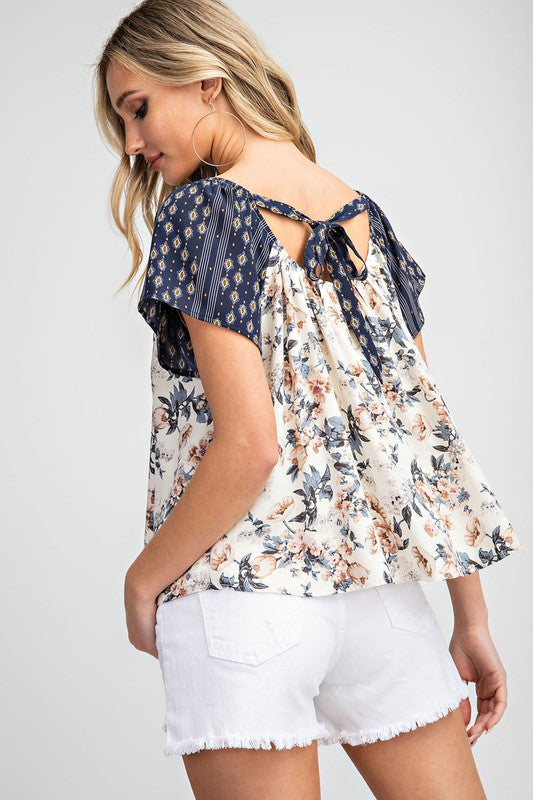 The perfect mix of color and fabric on this loose around the waist fitting swing top. Adorable back self tie details. Pairs with jeans and shorts perfectly. Poly. Model is 5'8