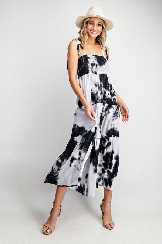 Our black smocked maxi dress has self tie shoulders at the square neck and a tiered ruffle skirt. Fun and flirty and ready for Summer. Fits true. Rayon. Model is a size 2, 5'8