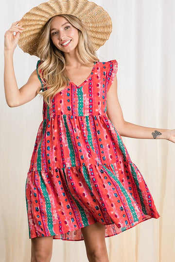 This flowy and fun swing dress has a red multi pattern and ruffle details at the arms. Scoop v neck and shirred detailing. Cotton. Model is 5'9