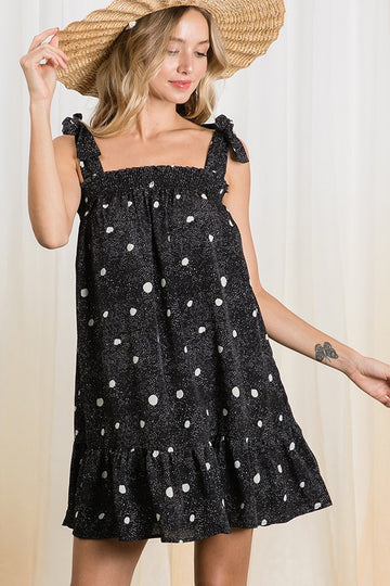 Brushstroke Polka Dot Dress For an easy everyday wearable summer look just throw on this flowy fit black dress with adorable brushstroke polka dots and tie detail shoulders. Poly. Model is 5'9