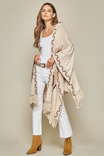 Awesome Embroidered Details! Throw this gorgeous upper line embroidered taupe fringe poncho over your tee and jeans for an easy and effortless style that will turn heads! Rayon/Nylon. Model is 5'9