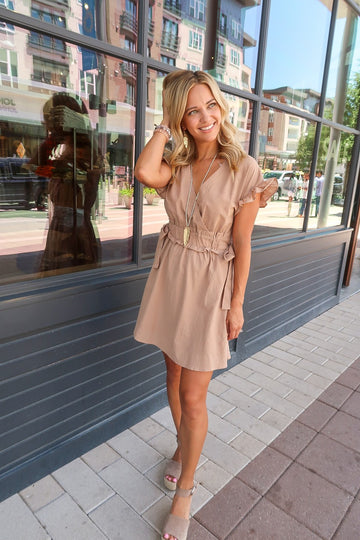 This taupe dress has a cute gathered waist and ruffle sleeve detailing. Great for work or for running around on the weekend. This dress gives a special feel to a classic look. Pair with sandals or booties for a summer to fall transitional style. Cotton. Model is 5'9