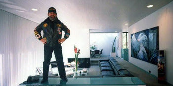Boscutti - Don Simpson - Don Simpson standing on a glass-topped desk in the living room of his home