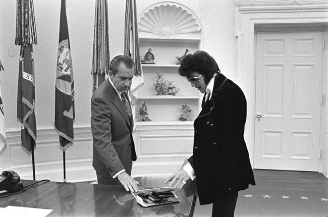 Boscutti - Elvis Presley - President Richard Nixon fingers through photos and citations Elvis Presley has brought to the oval office