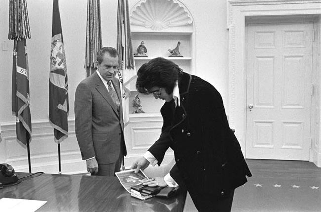 Boscutti - Elvis Presley - Elvis Presley pulls out a portrait of him with his daughter Lisa Marie Presley to show President Richard Nixon in the oval office