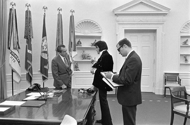 Boscutti - Elvis Presley - President Richard Nixon in discussion with Elvis Presley while While House aide Egil Krogh takes notes in the oval office