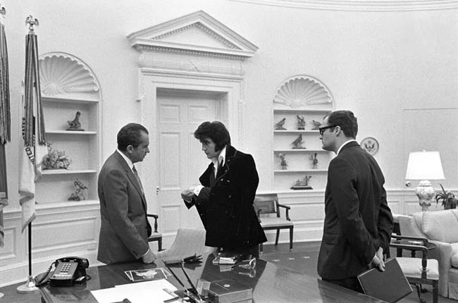 Boscutti - Elvis Presley - Elvis Presley shows President Richard Nixon his solid gold cufflinks while White House aide Egil Krogh looks on in the oval office