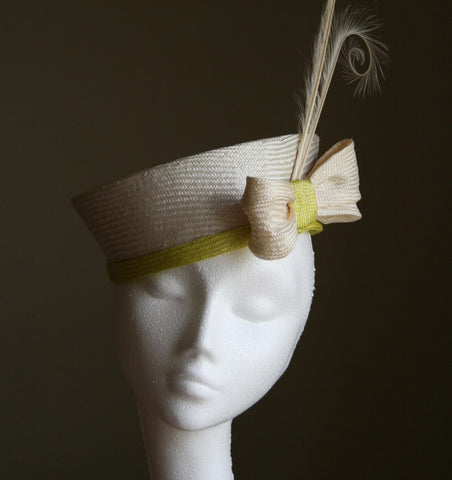 A Pillbox hat with bow and feathers