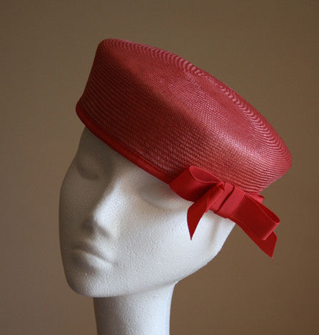 Red pillbox with red trim and bow