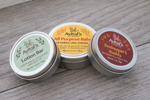 Three tins: Lotion Br (with green label), All Purpose Balm (with gold label), and Beekeeper's Buddy (with reddish brown label).