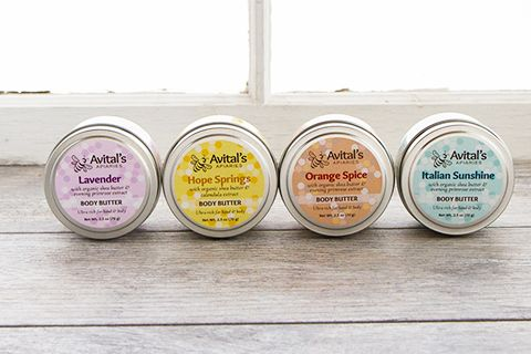 Four tins of Body Butter (Lavender, Hope Springs, Orange Spice, and Italian Sunshine) in front of a sunny window.