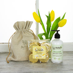 A glass bottle of Unscented Hand & body lotion and a package of Hope Springs Fizzies in front of a bright window and a vase of tulips.
