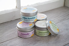 Tins of our Body Butter with a bright window behind them.