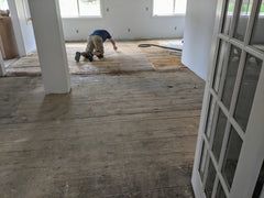 Old wooden floor being hand sanded and refinished.