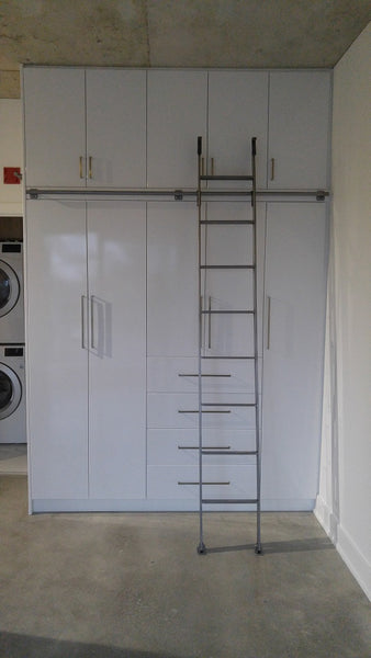 Modern white closet boasts custom built metal ladder and a 7ft long metal rail .  Ladder with multiple hooks was specially designed so it can be used not only for the tall  closet in the bedroom but also in the kitchen. Allowing  for maximum versatility on multiple rails and to store it elsewhere.