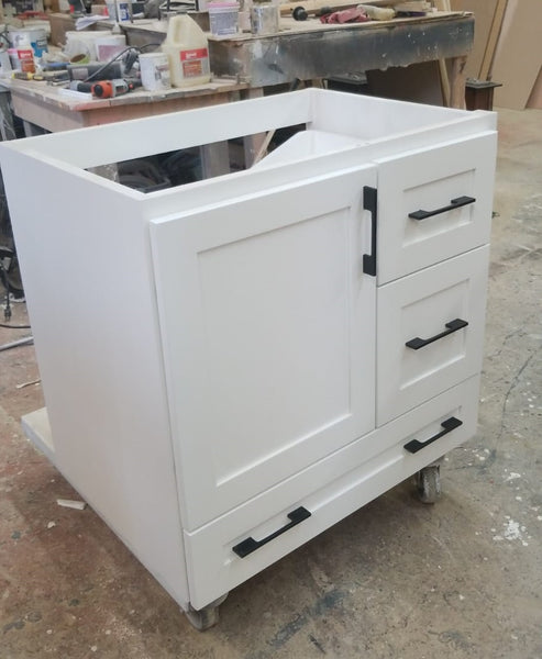 "Shown in the photos is a 30"" wide custom floating vanity designed to accommodate a off centered sink.  Cabinet built  from solid poplar wood.  Shaker style fronts.  Soft close drawers and doors.  Painted white.   30"" W x  18"" D x  32"" (ht)  Send us your rough sketch with dimensions along with your inspiration photos of your dream bathroom vanity,"