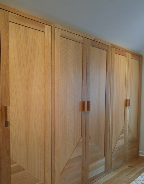 Custom storage solutions - Closet with solid oak wood doors, designed for a  room with ceiling at an angle.