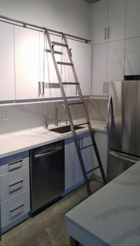 Modern white kitchen boasts custom built metal ladder and a 9ft long metal rail . Ladder with multiple hooks was specially designed so it can be used not only for the tall cabinets in the kitchen but also for the tall closet in the bedroom. Allowing for maximum versatility on multiple rails and when one wants to store it elsewhere.