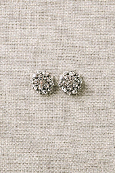 Closeup of sparkly bridal dome-shaped earring studs made with clear Swarovski crystals. Sara Gabriel.