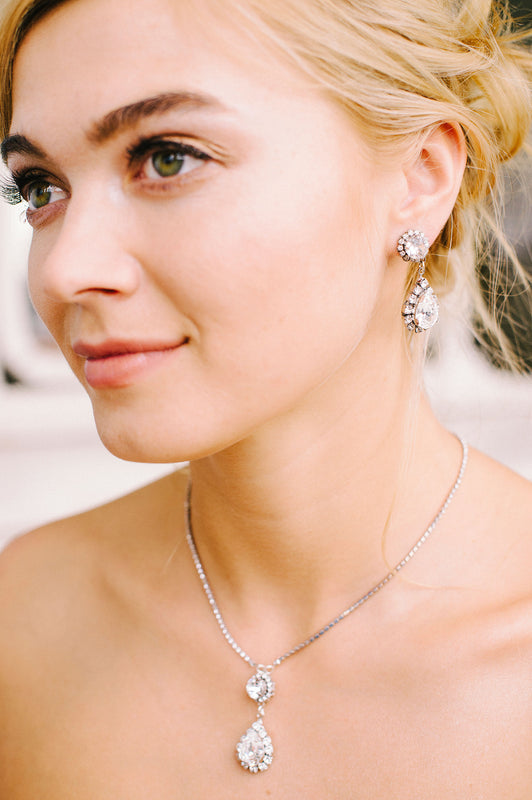 A bride wearing her sparkling silver drop earrings paired with her equally as stunning and matching teardrop pendant necklace both made with clear Swarovski crystals and crystal-set chain. Made by Sara Gabriel.