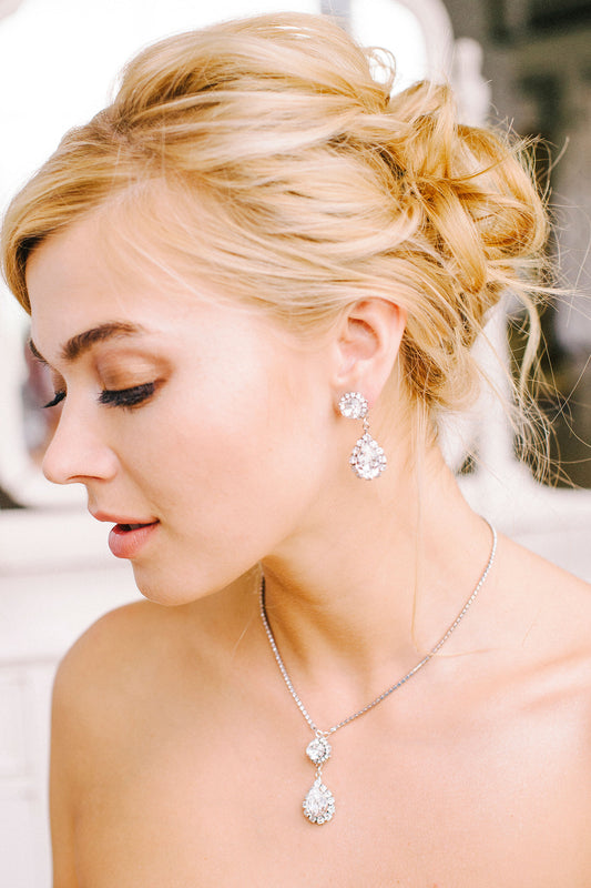 A bride wearing her sparkling silver drop earrings paired with her equally as stunning and matching teardrop pendant necklace both made with sparkling Swarovski crystals and crystal-set chain. Made by Sara Gabriel.