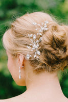 A bride with her head turned showing off her two, different sized hand-wired, leaf-shaped hair pins made with clear Swarovski crystals. Made by Sara Gabriel.