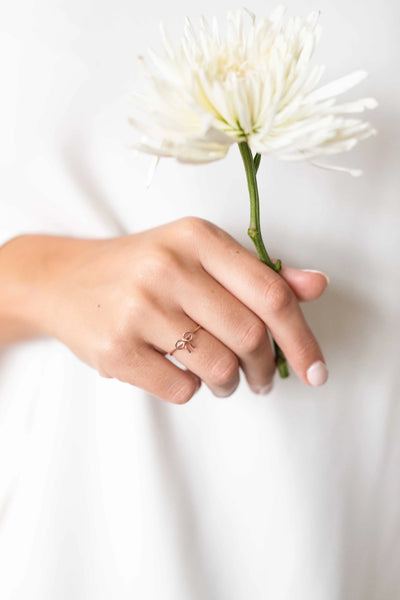 A hand holding a white, delicate flower with the focal point being a simple, bow-shaped ring plated in rose gold on the right, ring finger. Sara Gabriel.