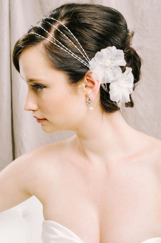 A bride with her head turned, looking to the right, wearing her delicate hair wrap made with freshwater pearls and the tiniest sparkling clear Swarovski crystals nestled inside two silk flowers. Made by Sara Gabriel.