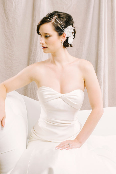 A bride in her white wedding dress sitting on a white couch, gazing to her right. She is wearing a stunning, delicate hair wrap along side her equally as gorgeous, sparkling earrings. Sara Gabriel